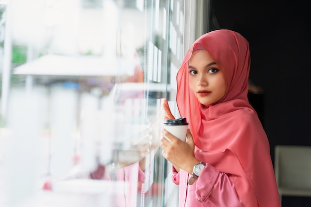 Beautiful young muslim business woman drinking coffee at workplace. portrait of young muslim pink hijab at co-work space. Premium Photo