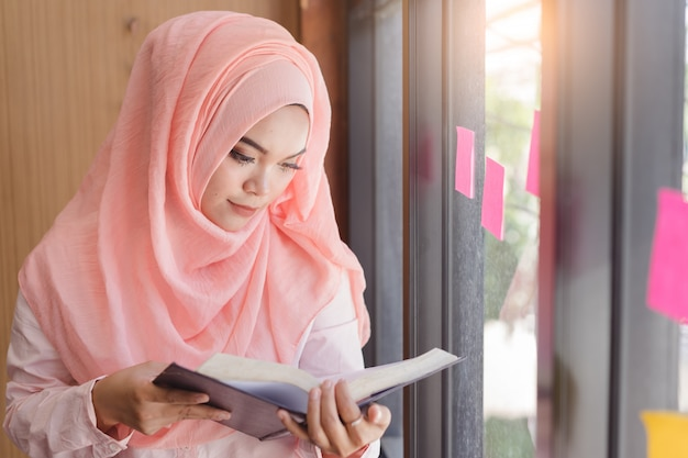 Beautiful young muslim woman reading a book in front of glass wall office. Premium Photo