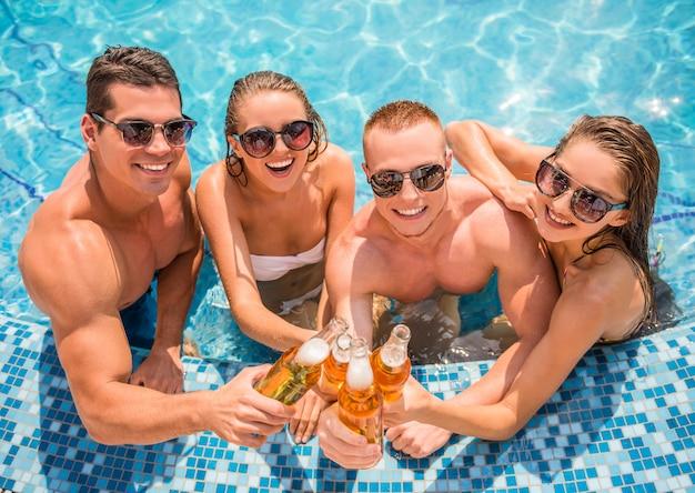 Beautiful young people having fun in pool. Premium Photo