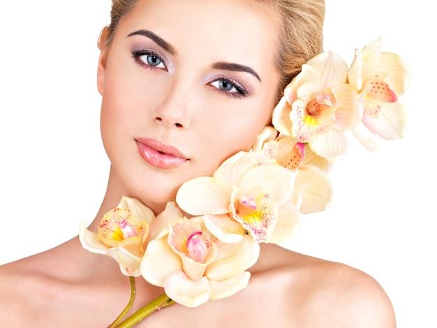 Красивая молодая красивая женщина со здоровой кожей и цветами рядом с лицом - изолированные на белом Бесплатные Фотографии