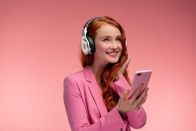 スマートフォンで音楽を聴いているヘッドフォンを持つ美しい若い赤毛の女性 Premium写真