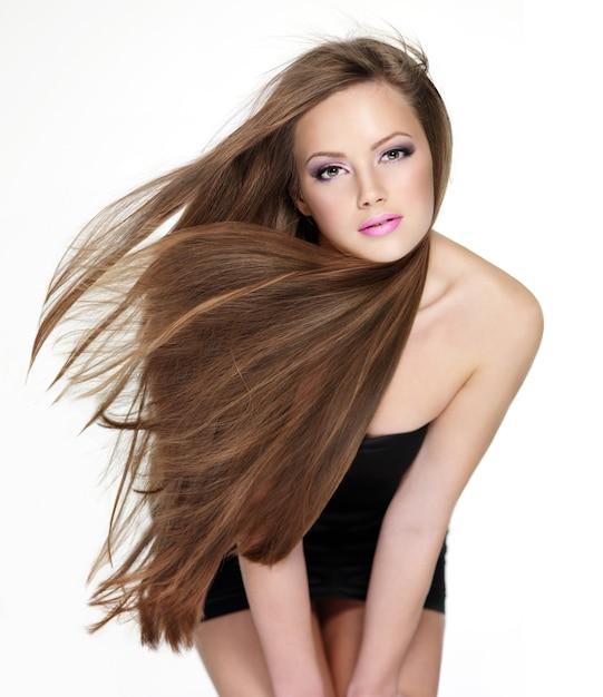 Bella giovane donna sensuale con lunghi capelli lisci su bianco Foto Gratuite