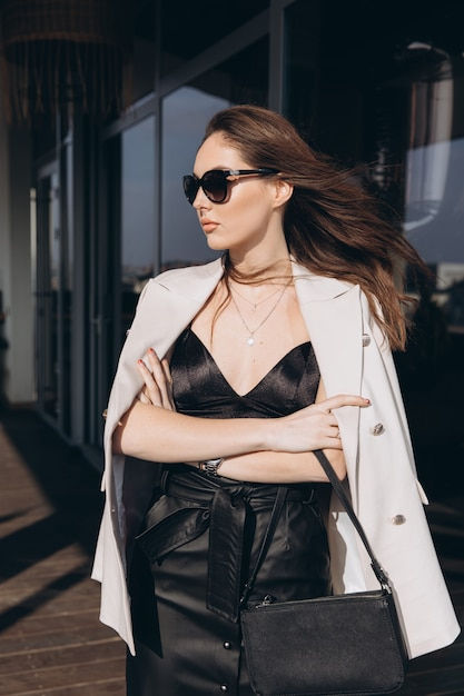 Beautiful young sexy woman in sunglasses, glamour girl in the white elegant jacket Premium Photo