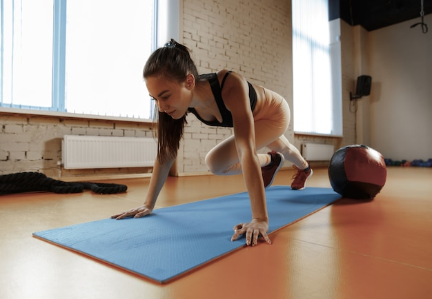 Beautiful young slim woman doing some gymnastics at the gym with medball. athlete, sport, rope, training, workout, exercises and healthy lifestyle concept Free Photo