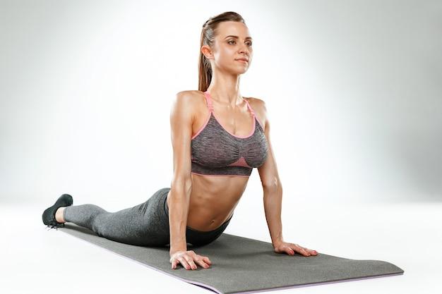 白い背景に、ジムでストレッチ体操を行う美しい若いスリムな女性 無料写真