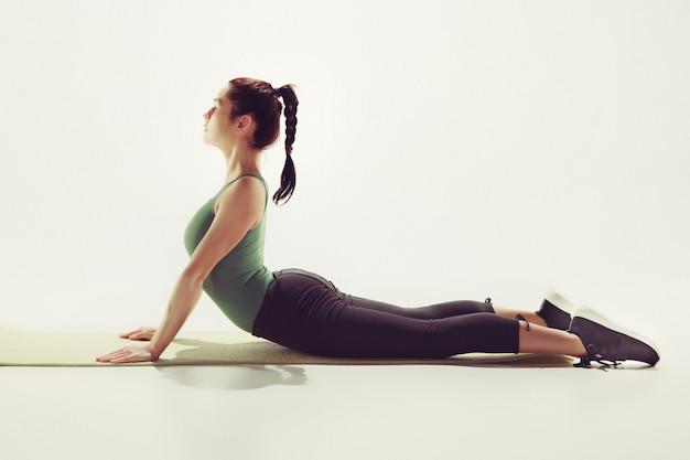 Красивая молодая стройная женщина делает упражнения на растяжку в тренажерном зале на фоне белой студии Бесплатные Фотографии