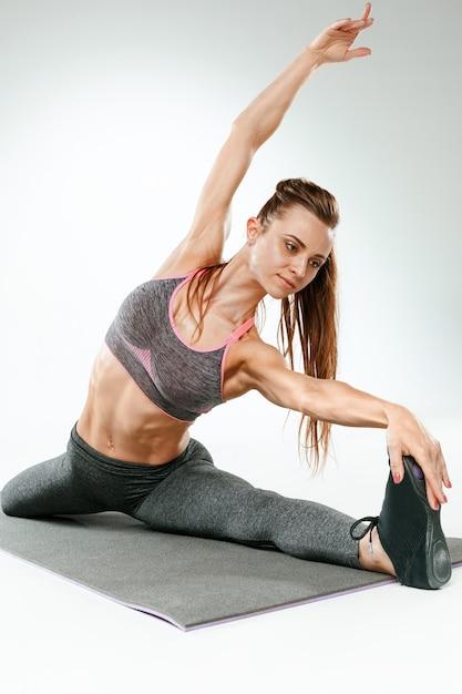 Красивая молодая стройная женщина делает упражнения на растяжку в тренажерном зале против белого Бесплатные Фотографии