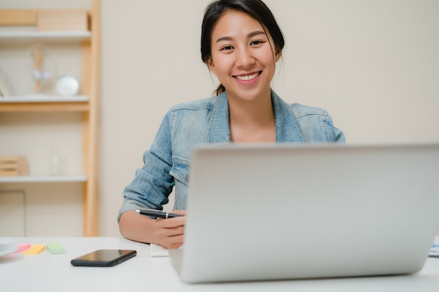 Beautiful young smiling asian woman working laptop on desk in living room at home. Free Photo