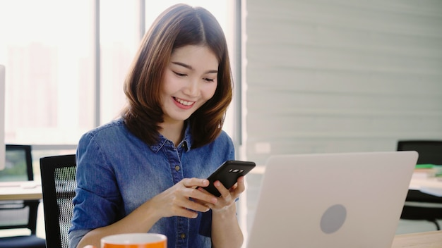 Beautiful young smiling asian woman working on laptop while enjoying using smartphone at office. Free Photo