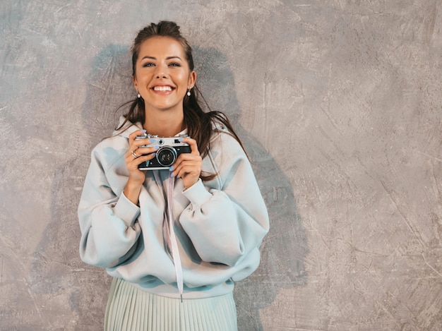 Beautiful young smiling photographer girl taking photos using her retro camera. Free Photo