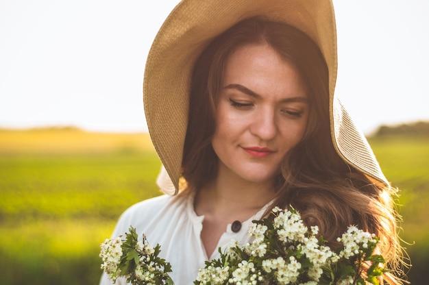 Красивая молодая улыбающаяся женщина в винтажном платье и соломенной шляпе в полевых цветах поля. девушка держит корзину с цветами Premium Фотографии