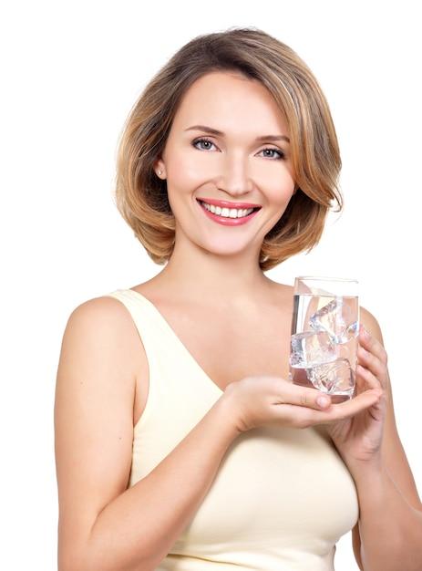 白い壁に水のガラスと美しい若い笑顔の女性 無料写真