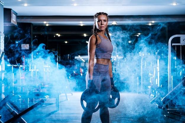 ジムで美しい若いスポーツウーマン Premium写真