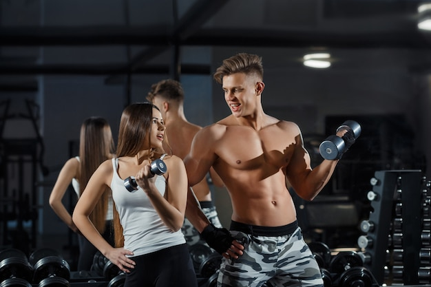 Beautiful young sporty sexy couple showing muscle and workout in gym during photoshooting Premium Photo