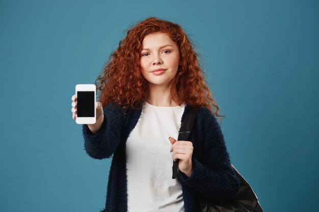 Bella giovane donna dai capelli rossi teenager con le lentiggini che mostra telefono cellulare, tenendo zaino con la mano, avendo sguardo felice e sicuro. Foto Gratuite