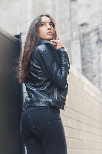 Beautiful young woman adjusting her leather collar jacket Free Photo