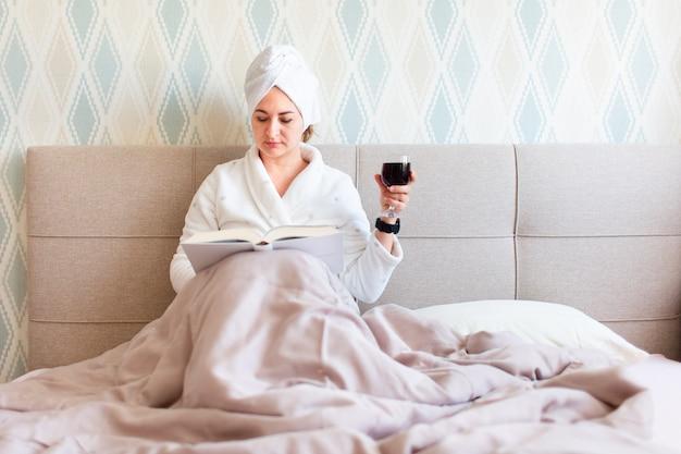 Красивая молодая женщина после душа в халате и с полотенцем на ее волосы. девушка лежит на кровати с бокалом красного вина в домашних условиях и читает книгу Premium Фотографии