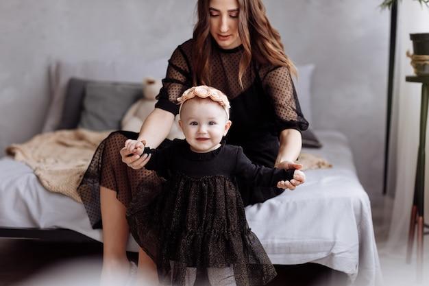 Красивая молодая женщина и ее очаровательная маленькая дочь обнимаются и улыбается на кровати Premium Фотографии