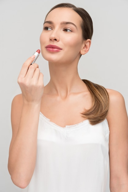 Beautiful young woman applying makeup Premium Photo
