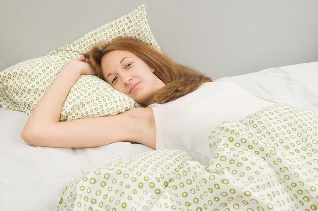 Beautiful young woman awake in bed Free Photo