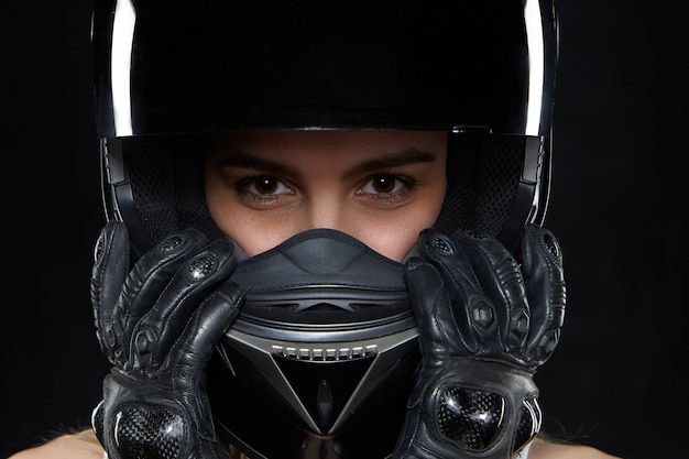 Beautiful young woman in black leather gloves and protective motorbike helmet. attractive self determined female motocycle racer wearing hands and body protection from falls and accidents Free Photo