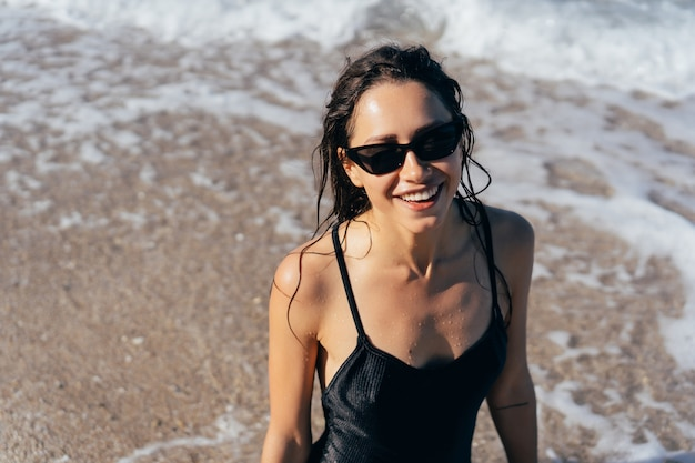 Beautiful young woman in black wet swimsuit Free Photo