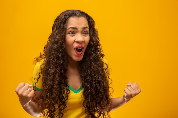 Beautiful young woman brazilian supporter with curly hair. Premium Photo