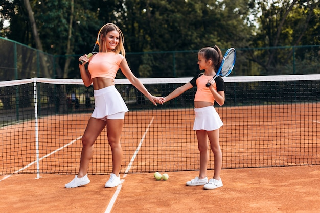 Beautiful young woman brought her daughter to the tennis court Premium Photo