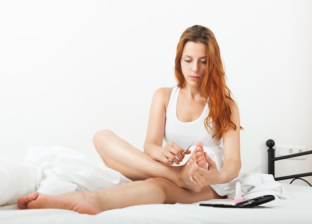 Beautiful young woman cares for toenails with nail lacquer Free Photo