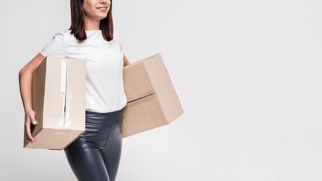 Beautiful young woman carrying cardboard boxes Free Photo