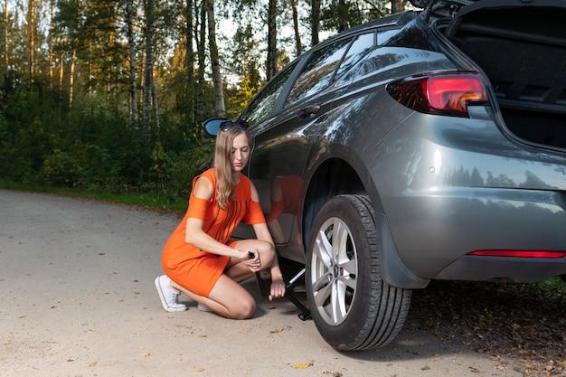 Beautiful young woman changing damaged wheel and fixing it Premium Photo