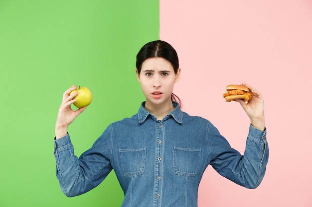Beautiful young woman choosing between fruits and unhelathy fast food at studio. Free Photo