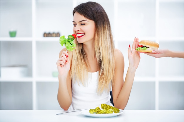 Beautiful young woman choosing between healthy food and junk food Premium Photo