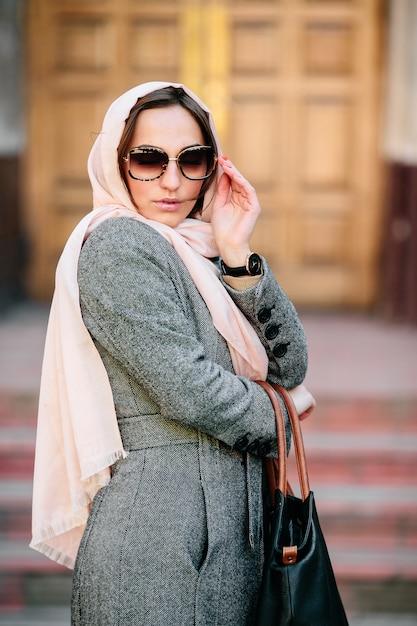 Bella giovane donna in un cappotto con una borsa in posa Foto Gratuite