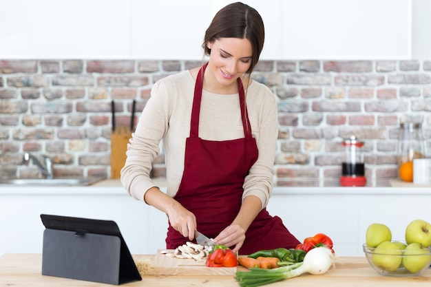 Beautiful Young Woman Cooking And Using Digital Tablet In The Kitchen. Free  Photo