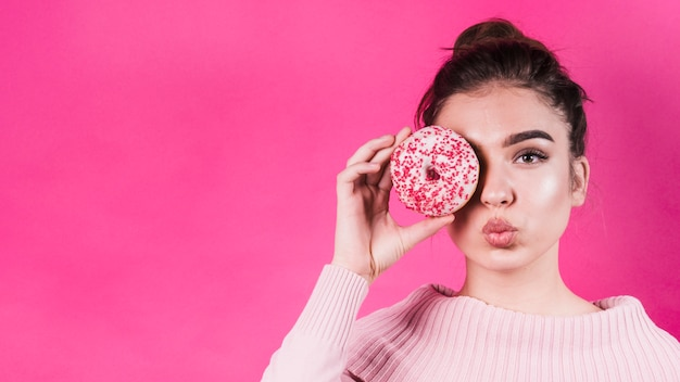 Beautiful young woman covering her eyes with delicious donut covering her eyes against pink background Free Photo