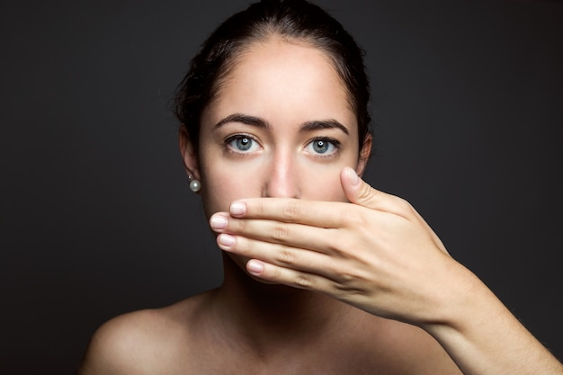 Beautiful young woman covering her mouth with hand. Isolated. Free Photo