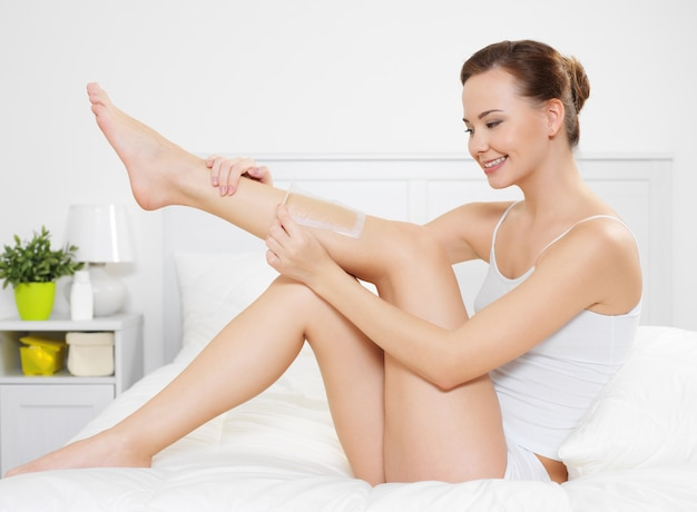 Beautiful young woman depilating skin on legs by waxing is in the bedroom Free Photo
