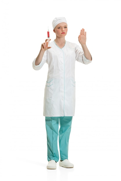 Beautiful young woman doctor in medical robe holding syringe in hand. Free Photo