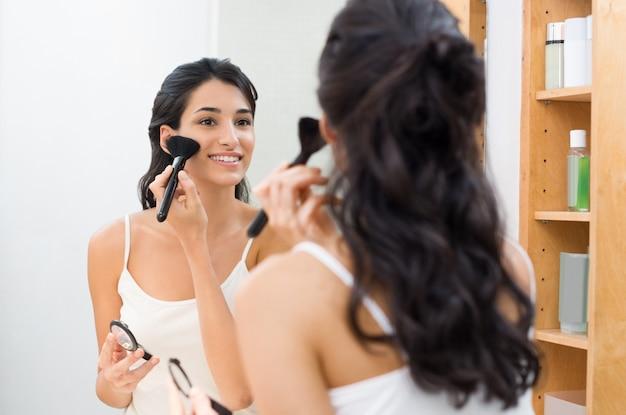 彼女のバスルームでメイクをしている美しい若い女性 Premium写真