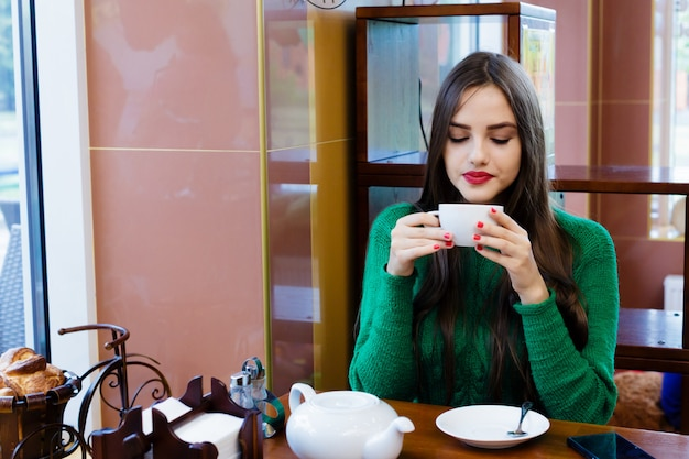 Beautiful young woman drinking tea in cafe Premium Photo