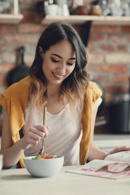 Красивая молодая женщина ест здоровый салат и читает журнал Бесплатные Фотографии