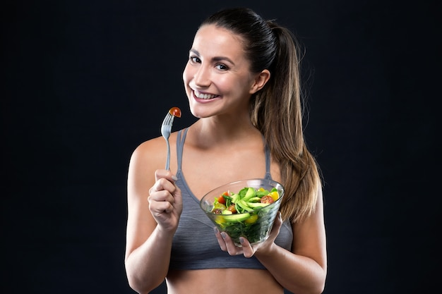 Beautiful young woman eating salad black background 1301 7563