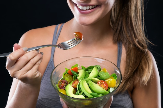 Beautiful young woman eating salad over black background 1301 7562