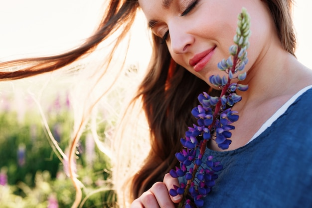Beautiful young woman face portrait in lupine field, holding flower near cheek. Free Photo