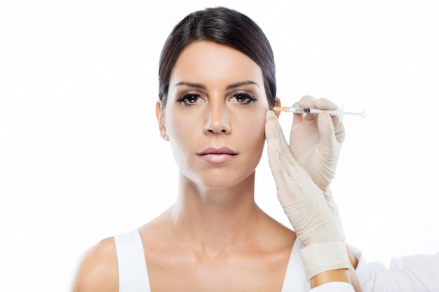 Beautiful young woman getting botox cosmetic injection in her face. Free Photo