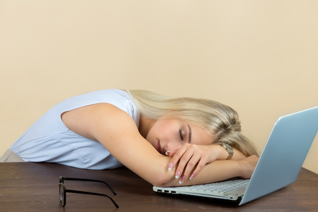 Beautiful young woman in glasses sleeps on a laptop Premium Photo