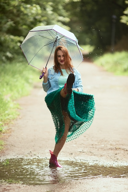 Beautiful young woman in green skirt has fun walking in gumboots on pools after the rain Free Photo