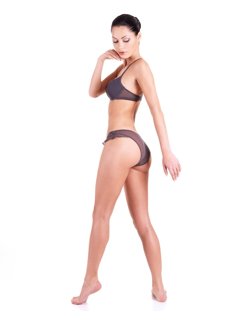 Beautiful young woman in a grey bikini with long legs standing isolated on white. Free Photo