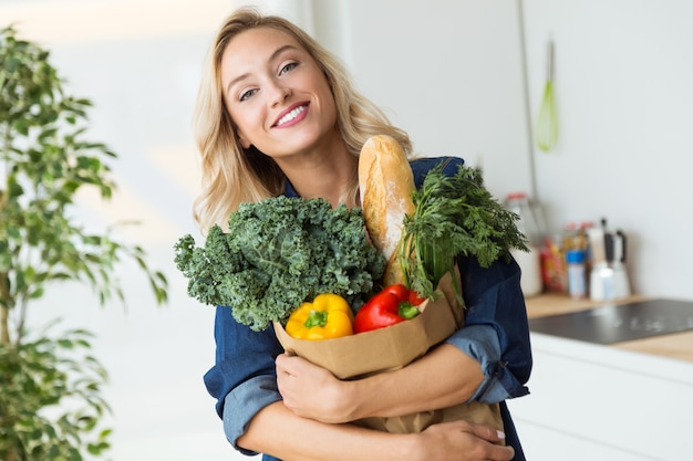 Beautiful young woman grocery shopping bag with vegetables at home. Premium Photo